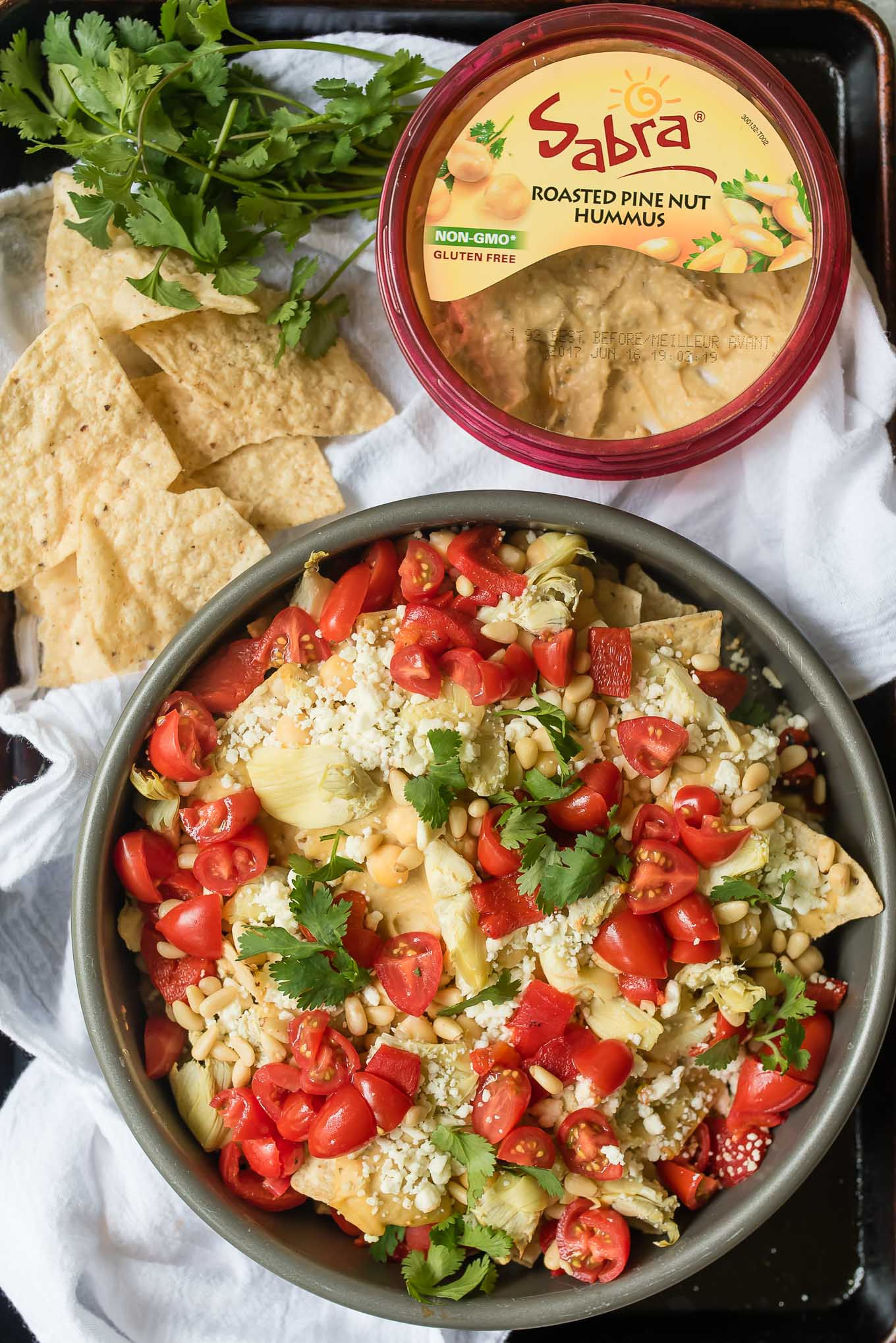 Mediterranean Nachos are a delicious gluten free and vegetarian snack/appetizer loaded with hummus, veggies, feta and more- a fun spin on the classic Tex Mex dish.